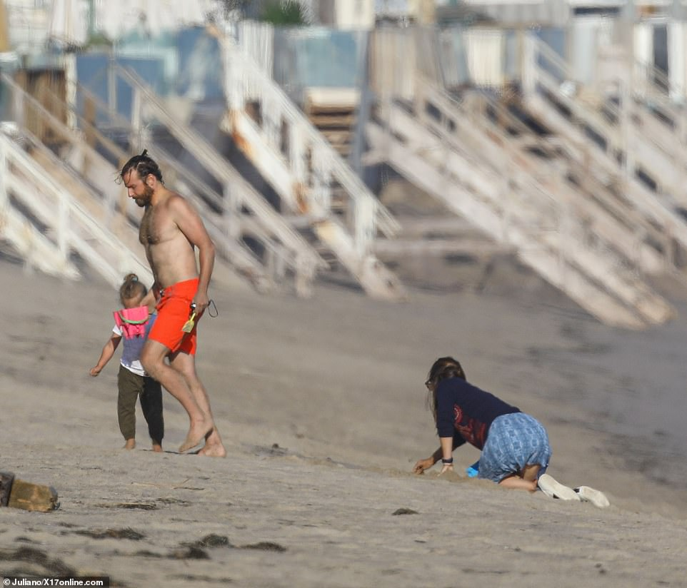 Cleaning up: Jen appeared to be gathering their things as they left the beach